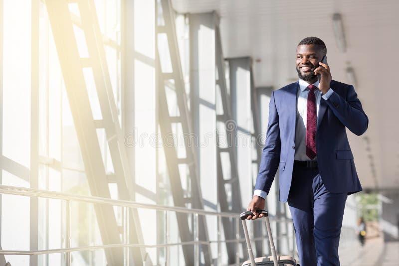 Путешественник бизнесмена говоря по телефону, идущ внутри аэропорта, чемодан нося стоковое изображение rf