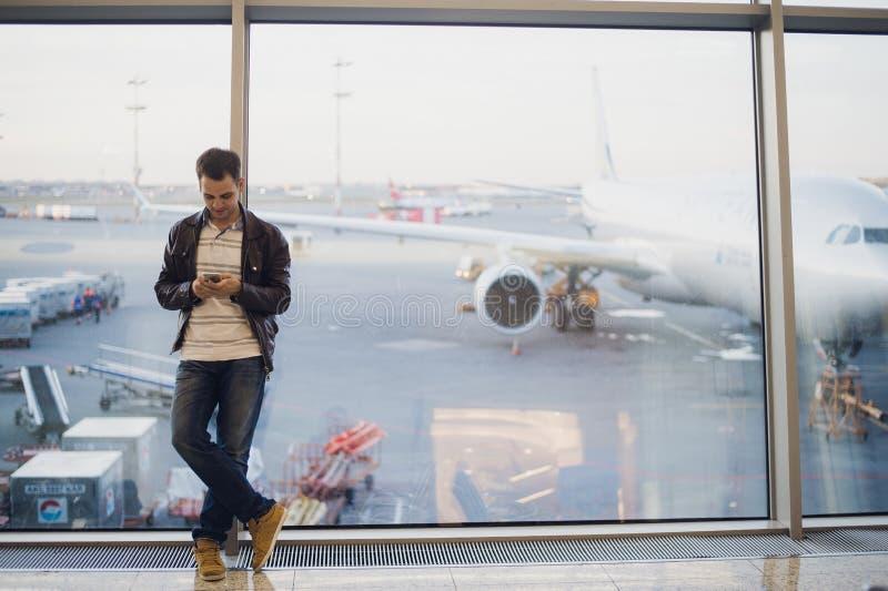Путешественник внутри крупного аэропорта Молодой человек используя мобильный телефон и ждущ его полет стоковое изображение rf