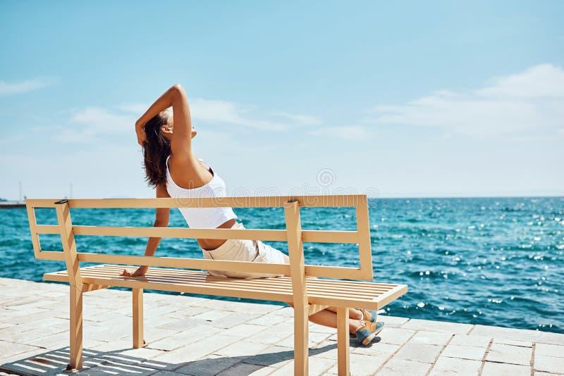 Путешественник девушки сидя на стенде около пляжа смотря море стоковая фотография