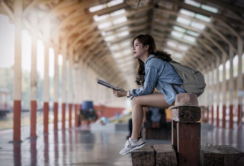 Путешественник женщины в голубых джинсах держа книгу и сидя на деревянной скамье стоковые изображения rf