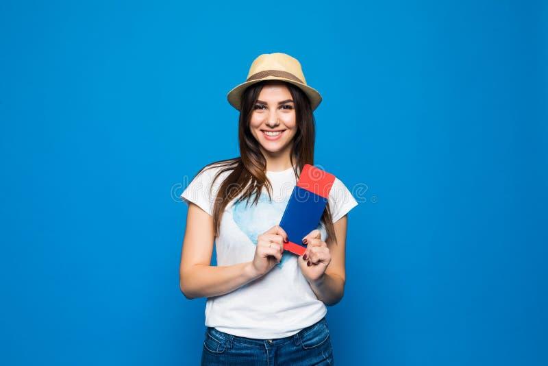 Путешественник женщины держа пасспорт с билетом Портрет усмехаясь счастливой девушки готовой для перемещения на голубой предпосыл стоковые изображения