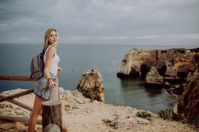 Путешественник женщины молодой красоты белокурый смотря море и скалу на красивом пляже Португалии перемещение и активная концепци стоковые изображения rf