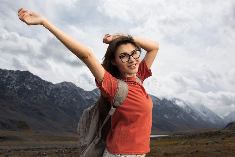 Путешественник женщины с рюкзаком усмехаясь задерживающ ее оружия Красота природы, снежных гор стоковые фото