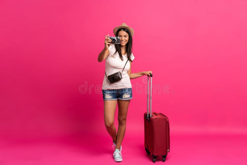 Путешественник женщины с чемоданом на предпосылке цвета стоковая фотография