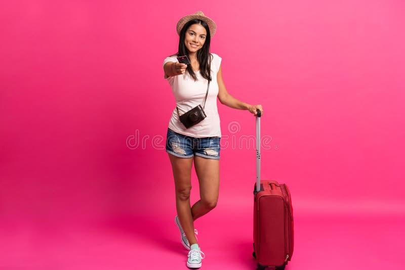 Путешественник женщины с чемоданом на предпосылке цвета стоковое фото rf