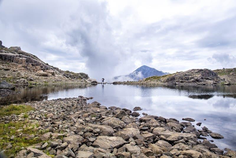 Путешественник идет в ландшафт панорамы с озером высоко в mou стоковые изображения rf