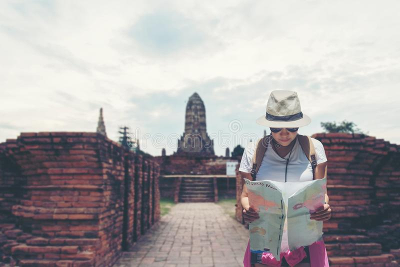 Путешественник и туристские азиатские женщины проверяют карту с рюкзаком идя в висок Ayuttaya, Таиланд стоковые изображения