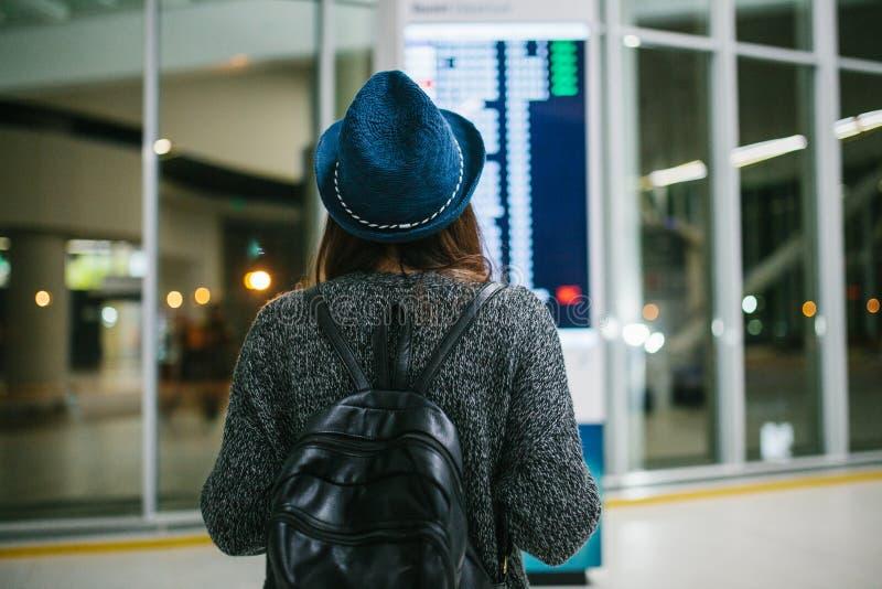 Путешественник маленькой девочки с рюкзаком в шляпе смотрит доску информации на авиапорте Получать информацию о стоковое изображение rf