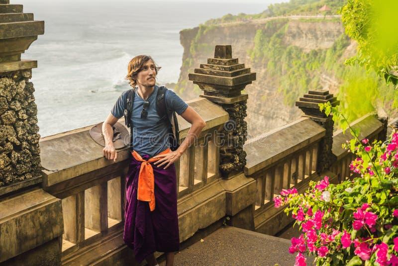 Путешественник молодого человека в виске Pura Luhur Uluwatu, Бали, Индонезии Изумительный ландшафт - скала с голубым небом и море стоковое изображение