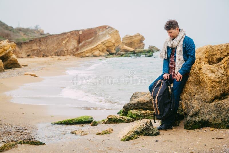 Путешественник молодого человека с положением рюкзака на утесе против красивого моря с волнами, стильный представлять мальчика хи стоковые фото