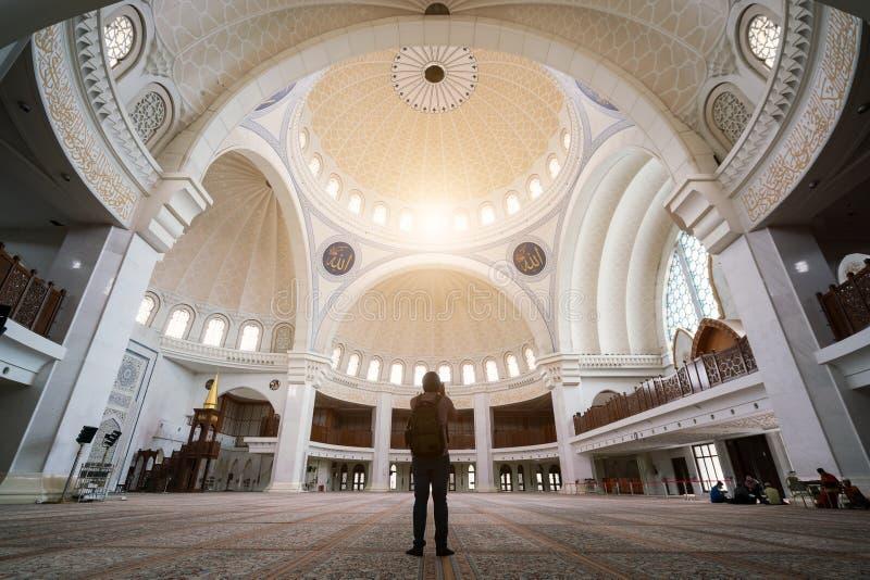 Путешественник молодого человека с рюкзаком идя к мечети Wilayah Persekutuan в Куалае-Лумпур, Малайзии стоковые изображения rf