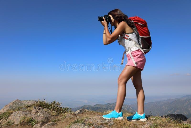 Путешественник молодой женщины принимая фото на горном пике стоковое фото rf