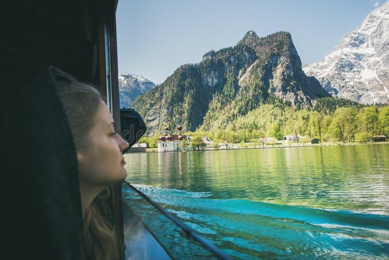 Путешественник молодой женщины смотря из окна на прогулке на яхте на озере Konigsee внутри berchtesgaden в Баварии, Германии стоковые изображения
