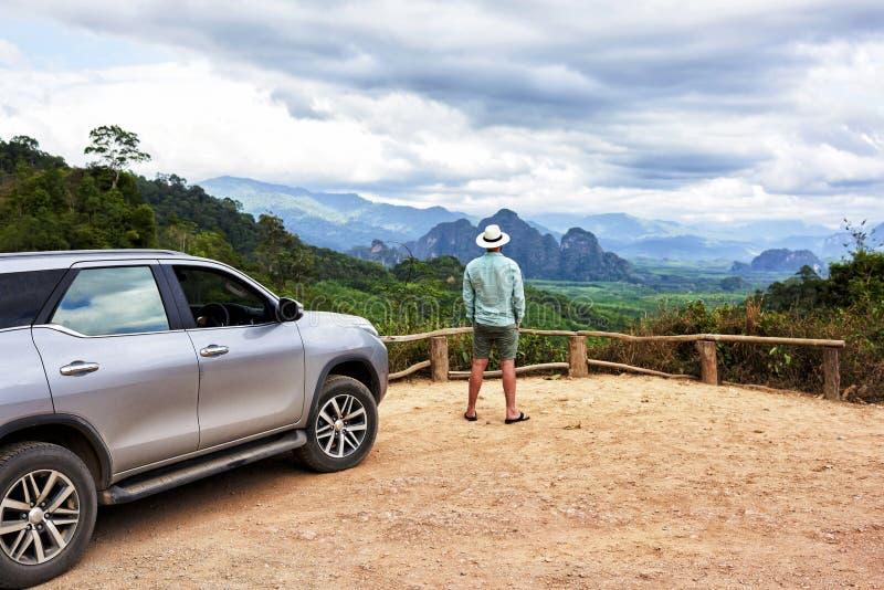 Путешественник молодого человека наслаждается шикарным взглядом во время его поездки на suv в Таиланде стоковое изображение rf