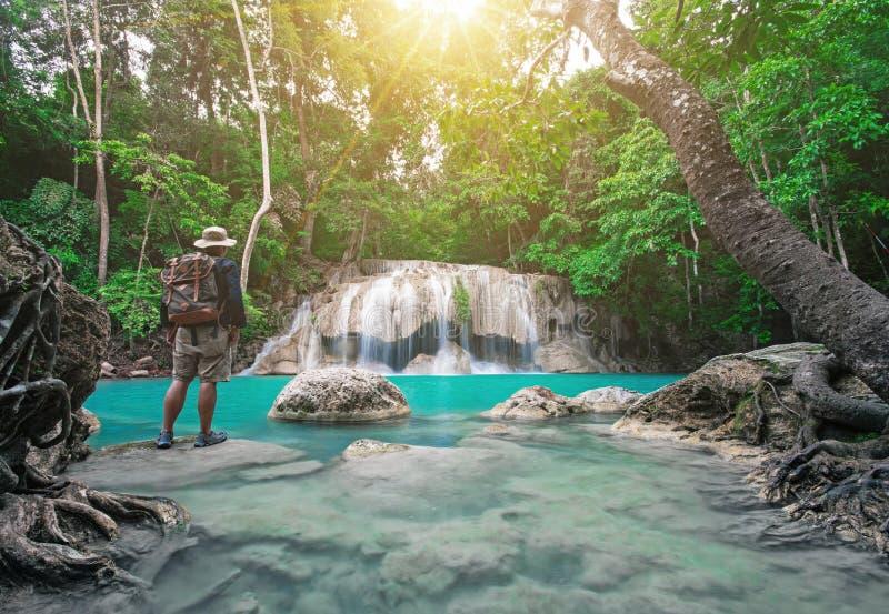 Путешественник наблюдает красивую предпосылку природы сцены от водопадов Earawan в Kanchanburi, Таиланде стоковое изображение