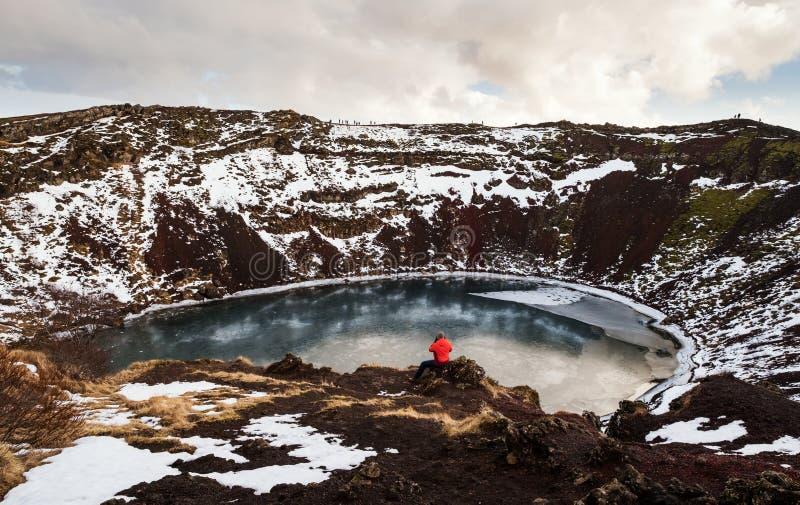 Путешественник наслаждаясь красивым видом на кратере Kerio с озером в Исландии стоковые фото