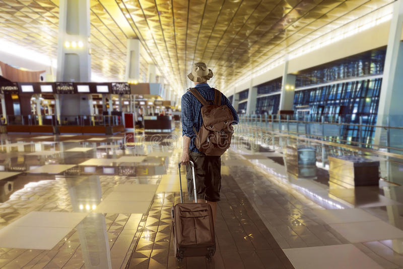 Путешественник носит его сумку в авиапорте стоковые фото