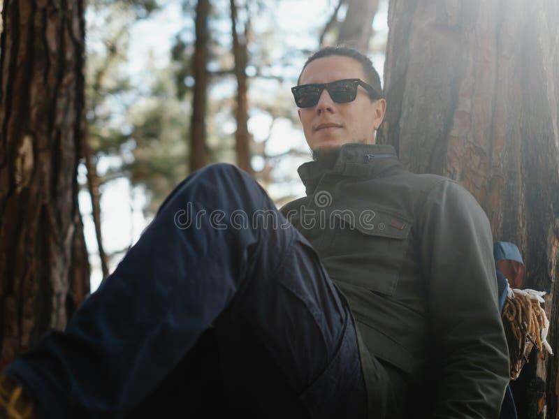 Путешественник отдыхая в лесе осени стоковая фотография