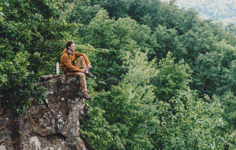 Путешественник отдыхая na górze скалы стоковые изображения rf