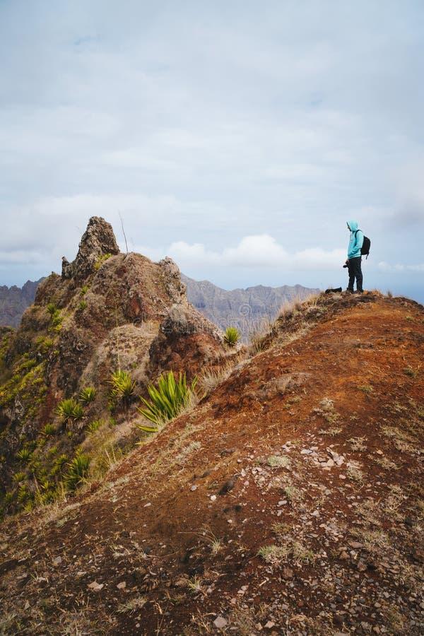 Путешественник при рюкзак рассматривая горные пики Сногсшибательный засушливый ландшафт острова Santo Antao, Cabo Verde стоковое изображение