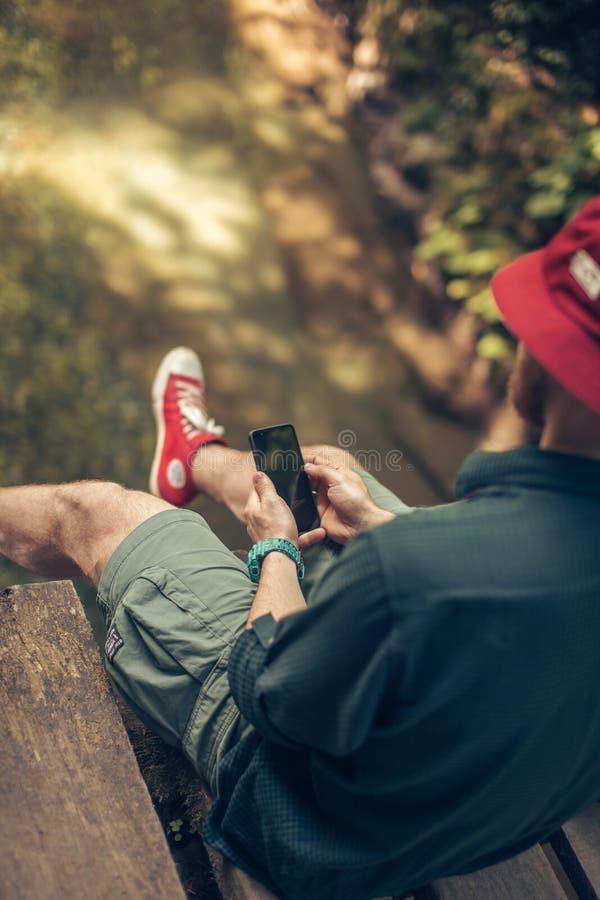 Путешественник сидит на деревянном мосте и использует smartphone для того чтобы увидеть карту для проводить стоковое изображение rf