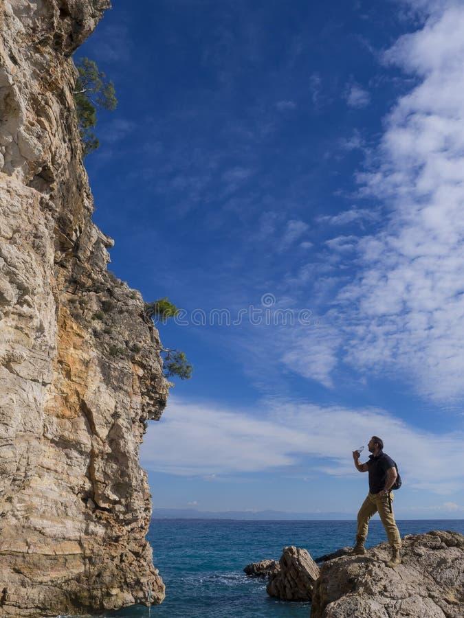 Путешественник с рюкзаком на утесах около моря смотря прочь Каникулы перемещения лета Красивый молодой кавказский турист стоковое изображение