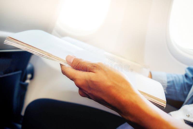 Путешественник читая кассету в самолете, стоковые изображения rf