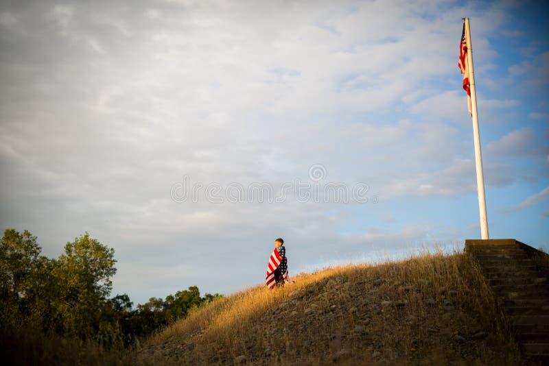Путешествие к свободе Молодой мальчик с американским флагом, утеха быть американцем стоковое фото rf