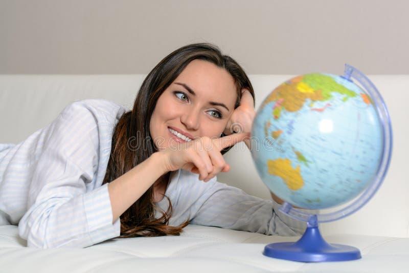 Путешествие Маленькая девочка в пижамах лежа на кресле, закручивая глобус с странами мира стоковые изображения