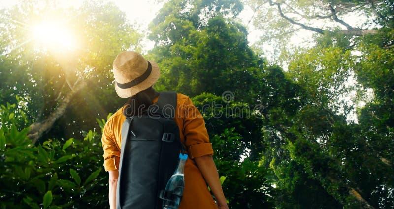 Путешествовать женщина с рюкзаком наслаждаясь на исследовать и trekking в тропическом лесе Азии, туристский путешественник на пре стоковые фото