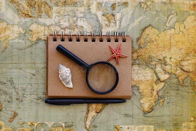 Путешествуйте плоское положение с лупой блокнота и plac seashells стоковая фотография