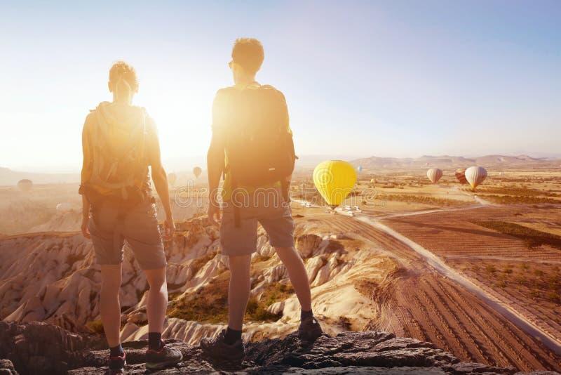 Путешествуйте предпосылка, пара путешественников смотря панорамный эффектный красивый вид гор стоковые фото