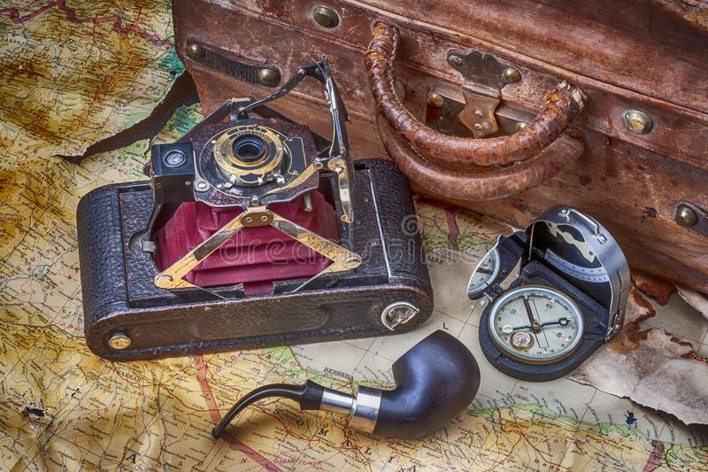 Путешествуйте, рискуйте, исследование с годом сбора винограда камеры складывая, старый чемодан, компас и карта с трубой табака бесплатная иллюстрация