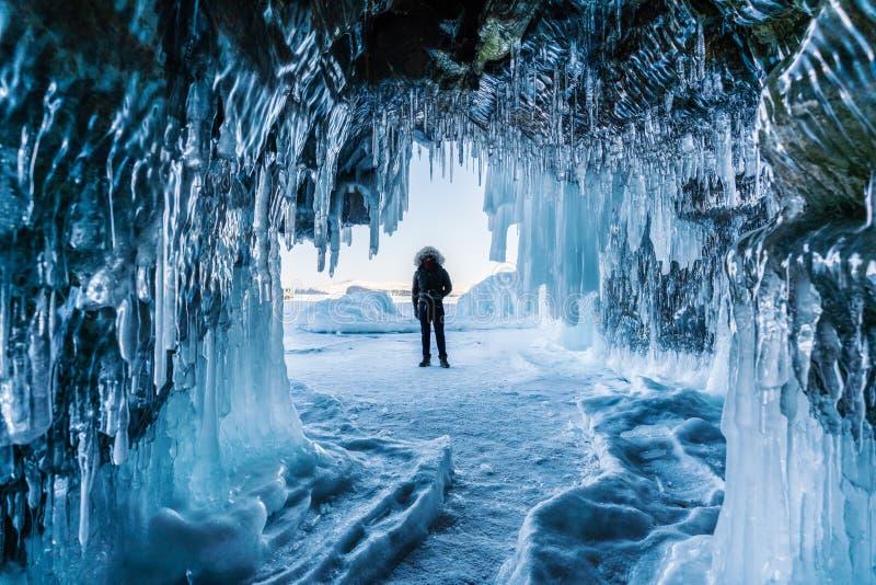 Путешествующ в зиме, человек стоя на замороженном Lake Baikal с пещерой льда в Иркутске Сибире, России стоковая фотография rf
