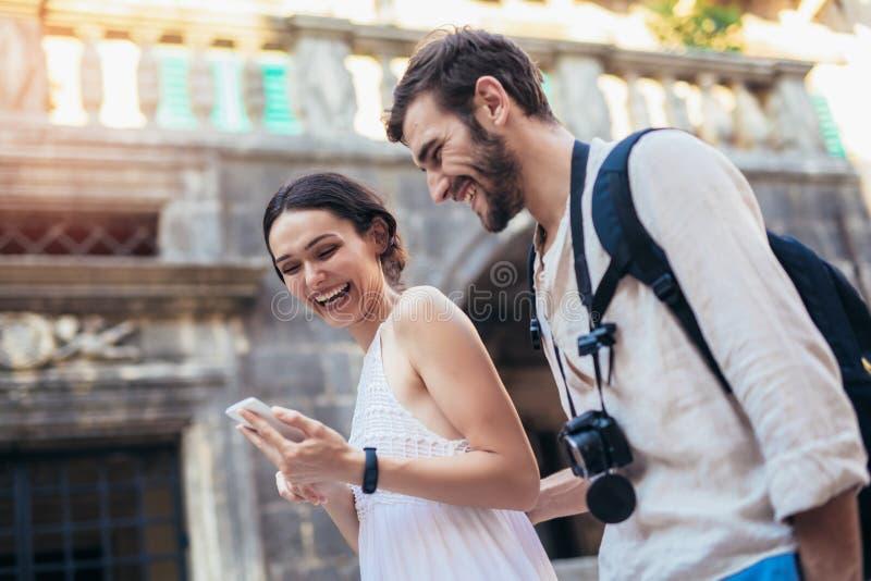 Путешествующ пары туристов идя вокруг старого городка, и использование умного телефона стоковые изображения rf