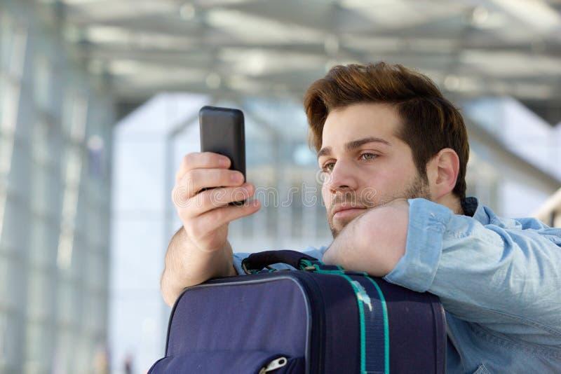 Путешествующ человек ждать на станции и смотреть мобильный телефон стоковая фотография rf