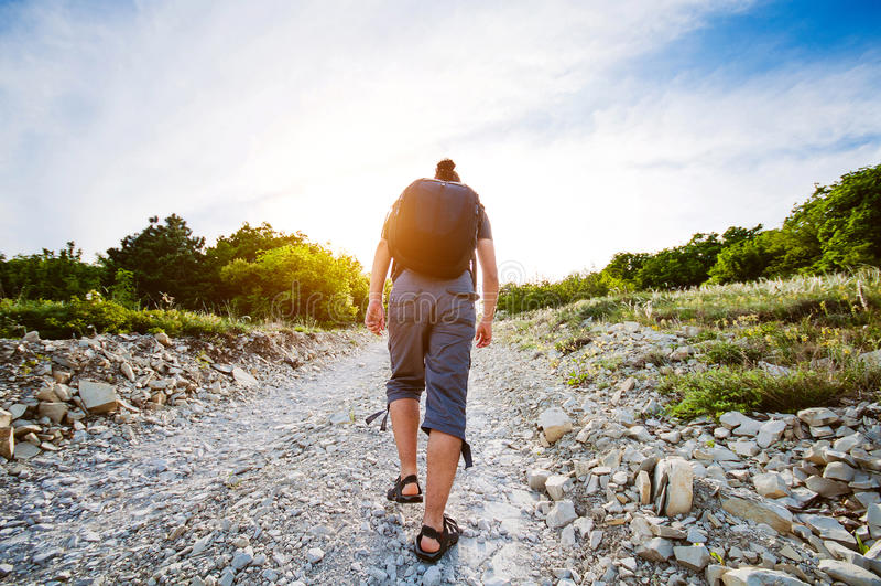 Путешествующ человек поднимая вверх для скалистой дороги стоковое фото rf
