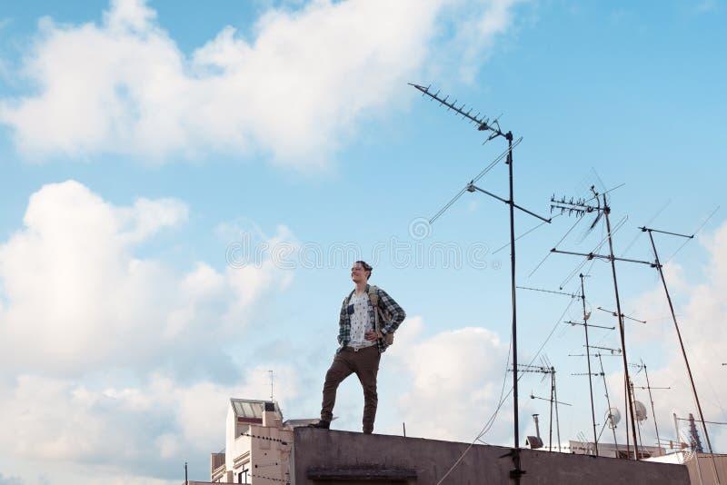 Путешествующ человек стоя на крыше, усмехаясь и смотря далеко с ярким голубым небом и белыми облаками и антеннами стоковые фото