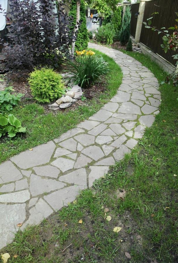 Путь вымощенный с естественным камнем в саде осени внутренний двор вымощен с декоративным серым естественным камнем стоковое фото