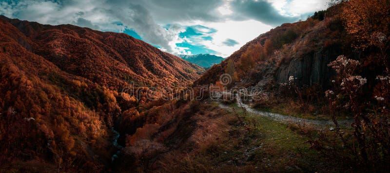 Путь который идет вдоль River Valley окружил горами против голубого неба с облаками Уайта стоковые фото