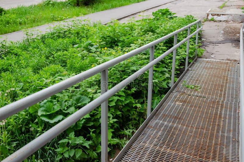 Путь пандуса с поручнем нержавеющей стали для людей с ограниченными возможностями кресло-коляскы поддержки стоковые изображения rf