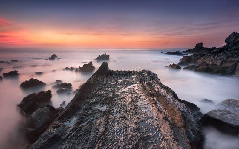 Путь утеса к океану, относительно красочного захода солнца стоковые фото