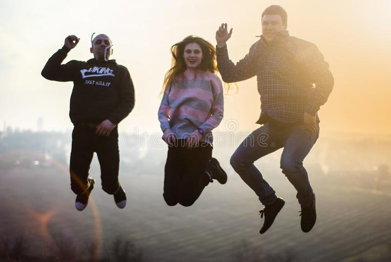 Путь Millennials образа жизни скача на солнце захода солнца горы стоковая фотография