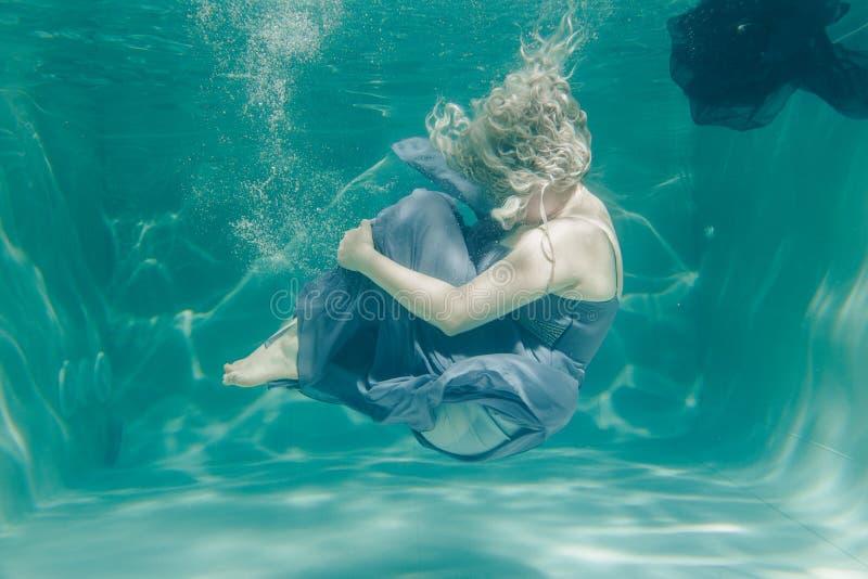 Пухлая женщина в сером выравниваясь длинном платье плавая под водой на ее праздниках и насладиться с ослабляет стоковая фотография rf