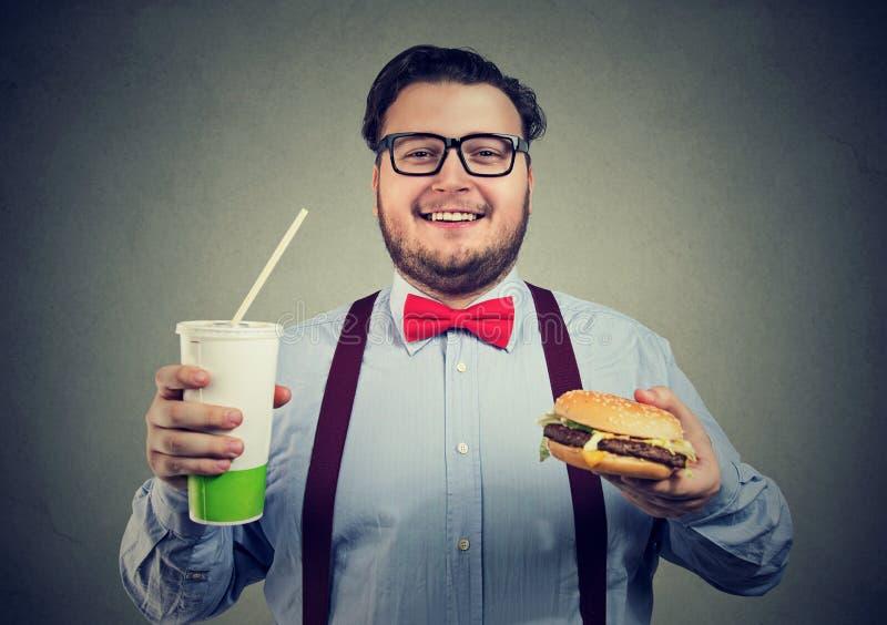 Пухлый человек представляя с фаст-фудом стоковое изображение