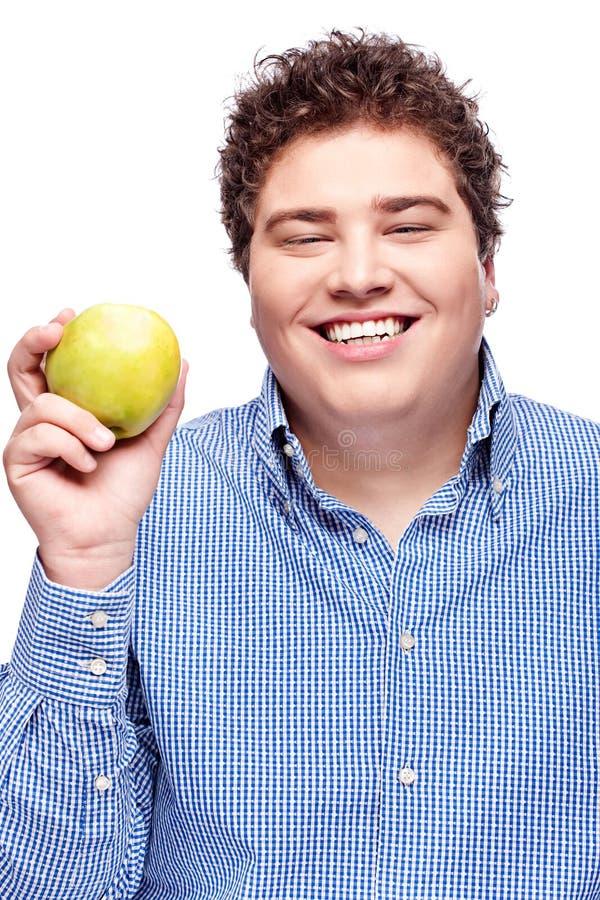 Пухлый человек держа яблоко стоковая фотография