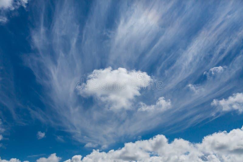 Пушистые белые облака через голубое небо r стоковая фотография