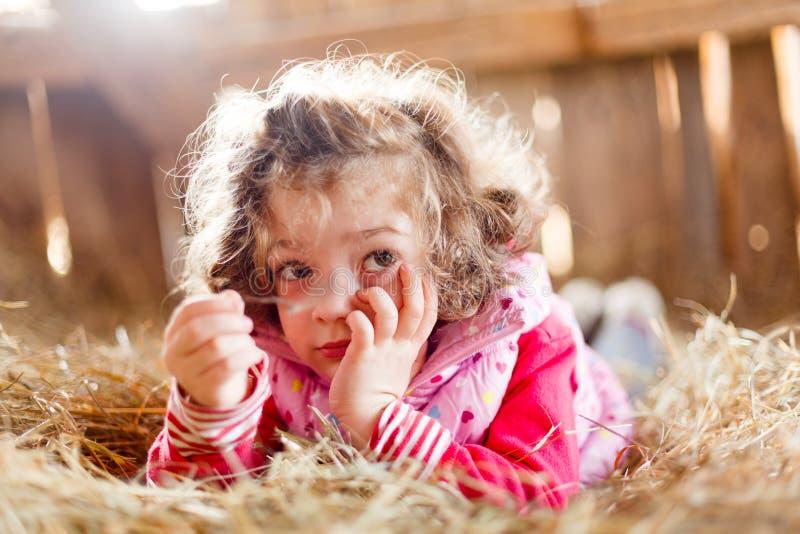 Пушистый с волосами ребенок в сене стоковая фотография