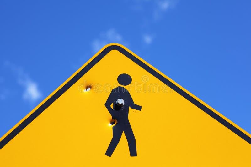 Пулевые отверстия в пешеходном знаке стоковые изображения