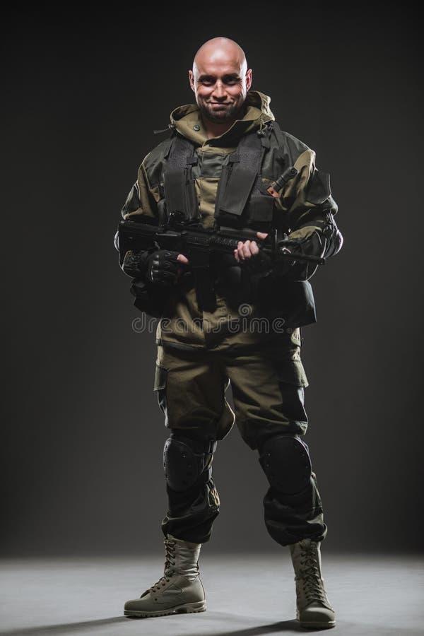 Пулемет владением человека солдата на темной предпосылке стоковые изображения rf